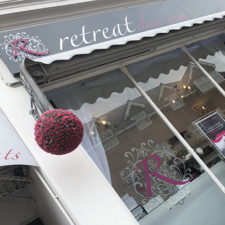 Shopfront fascia with a fret cut acrylic 'R' and etch vinyl window graphics.